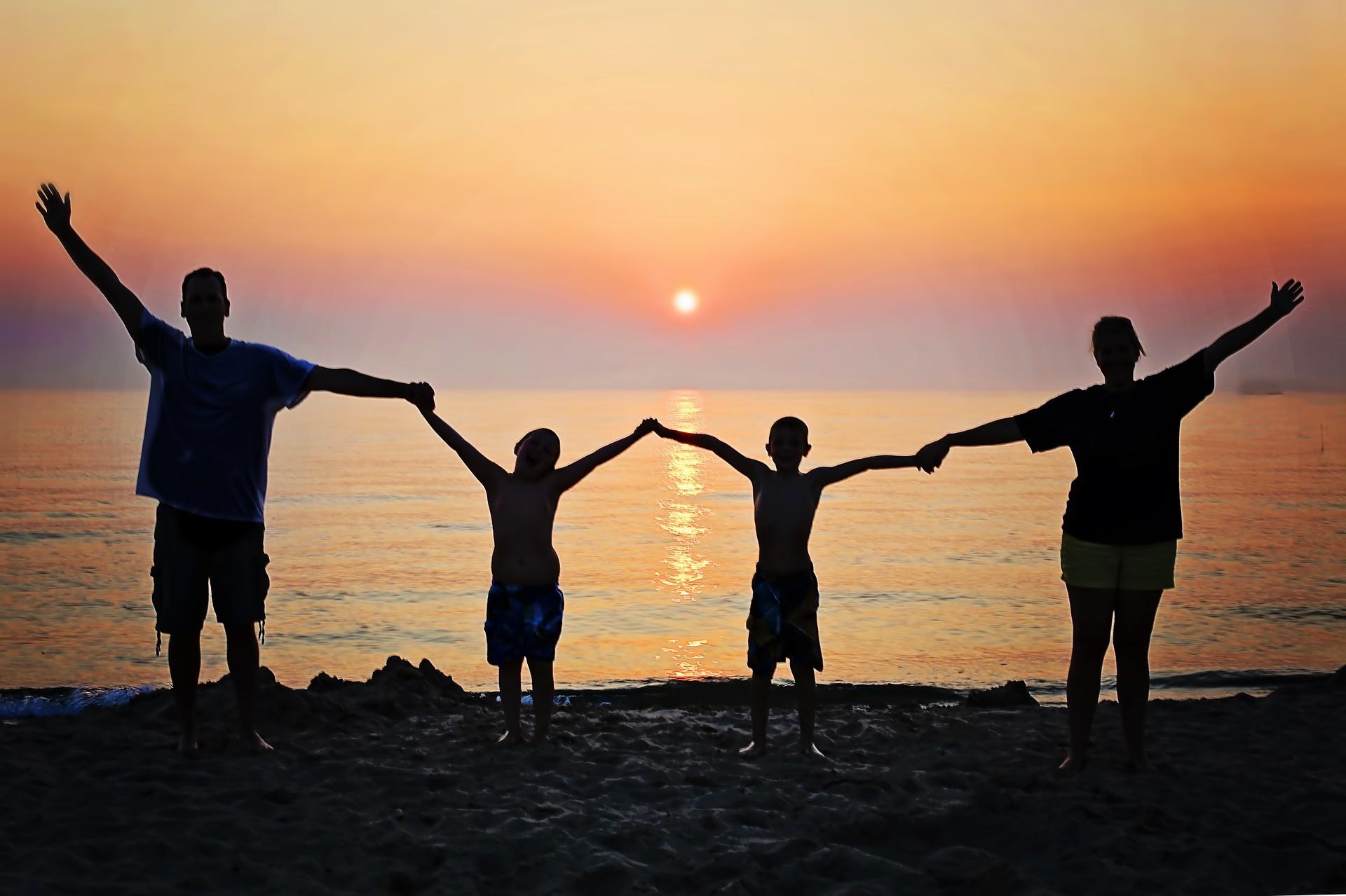 Foto: Familie händehaltend im Sonnenuntergang
