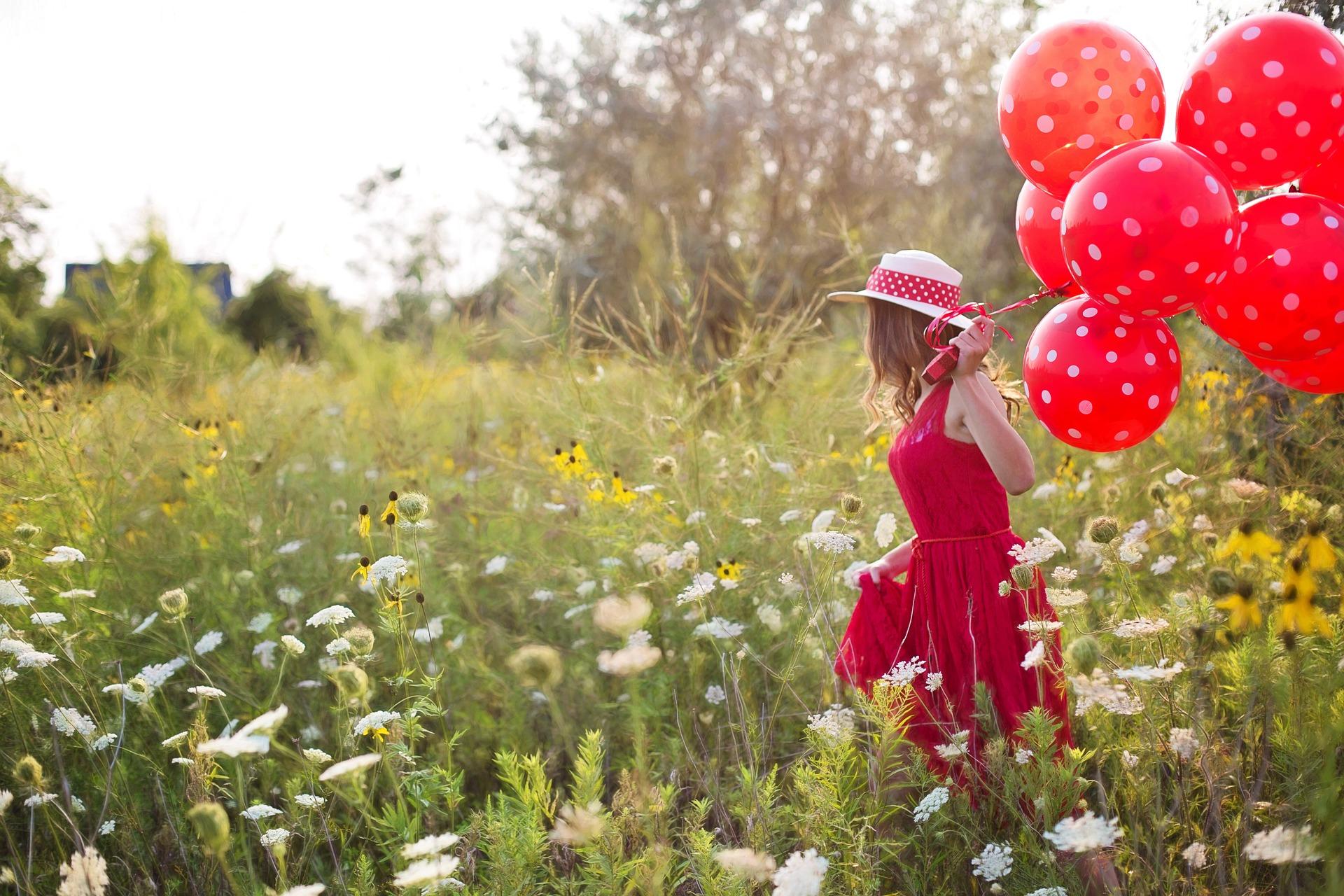 Foto: Frau mit rotem Kleid und Luftballons läuft durch eine Blumenwiese