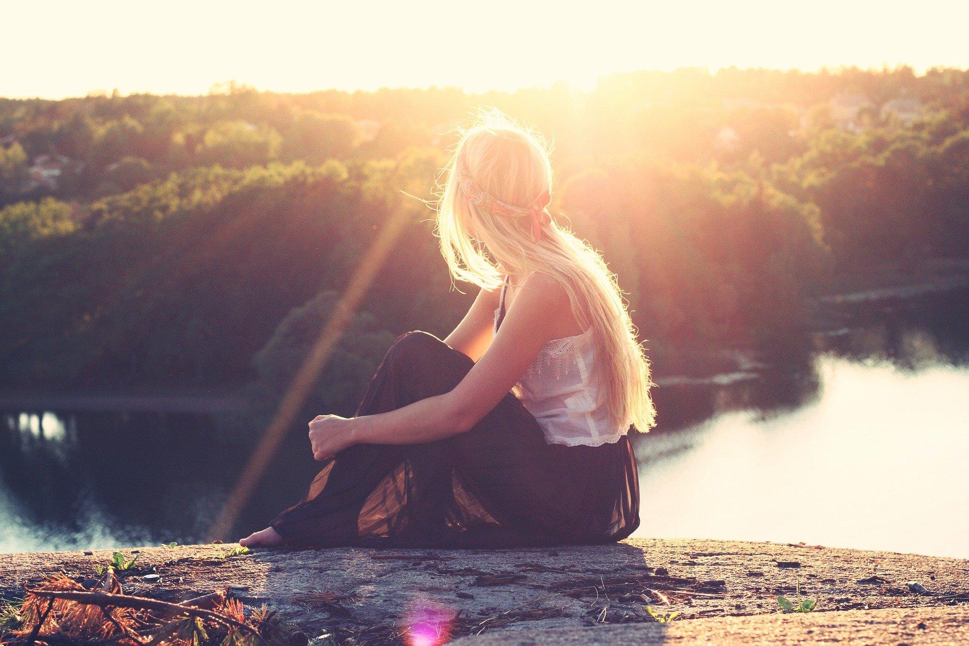Foto; Frau sitz auf einer Kante oberhalb eines Sees und wird von der Sonne angestrahlt
